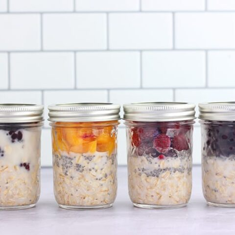 Overnight oats lined in mason jars on a white counter