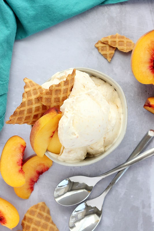 peach ice crema in a white bowl with waffle cone and sliced peaches on top