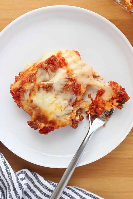 square of cooked lasagna on white plate with bite cut onto fork