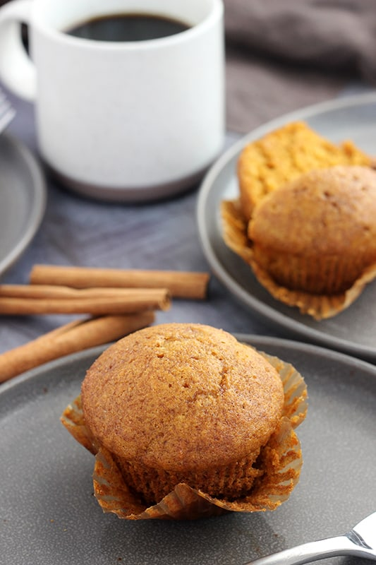 pumpkin muffin on grey plate with wrapper pulled down