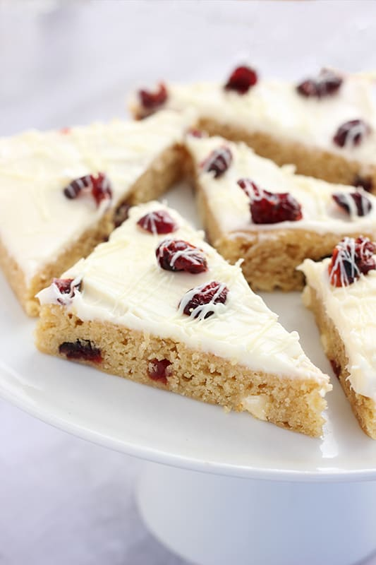 slice of cranberry bliss bars on white cake tray