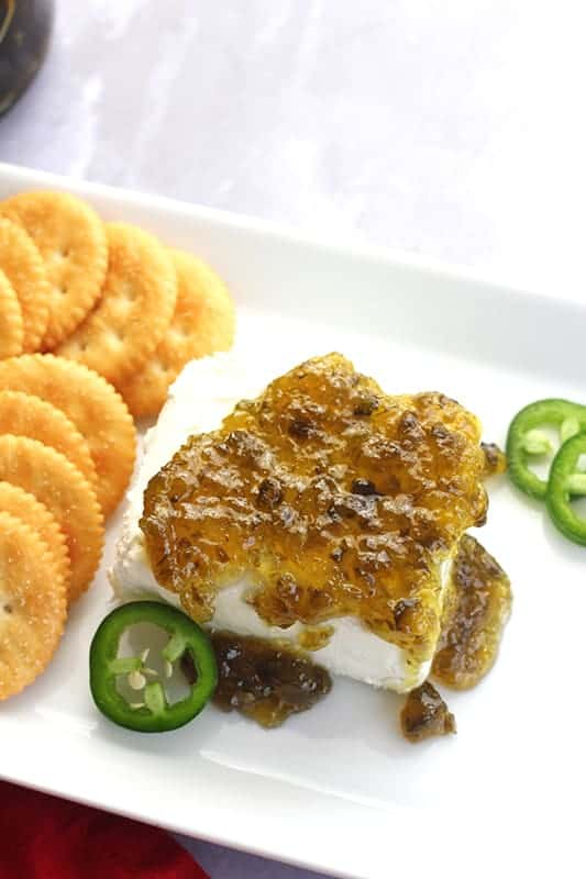 Jalapeno jelly over block of cream cheese with crackers