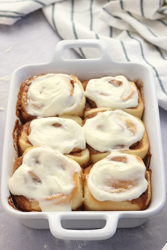 cinnamon rolls baked and frosted in a white pan