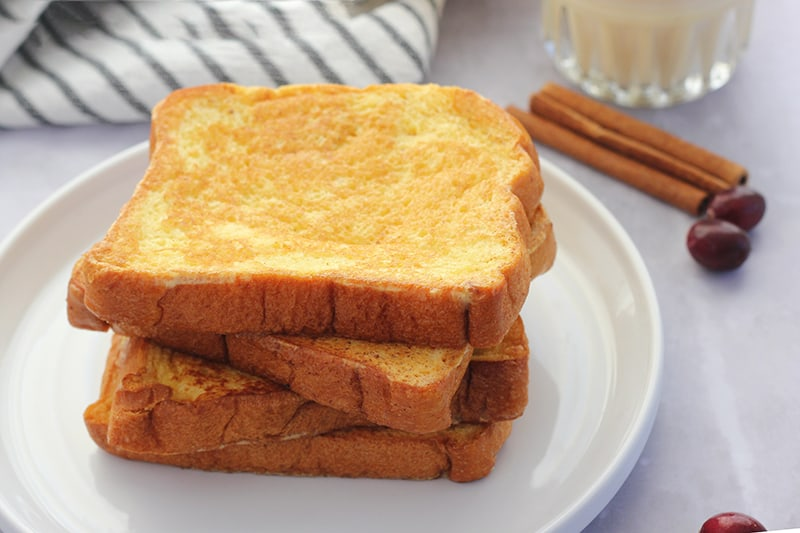 Eggnog french toast stacked on a white plate