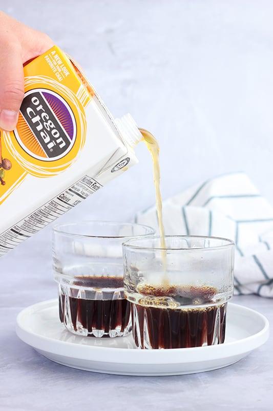 Chai tea being poured over espresso