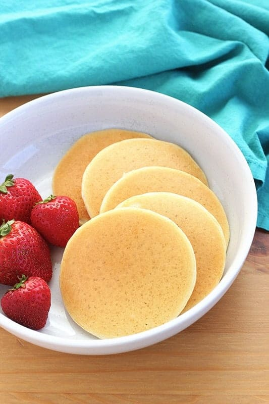 mini pancakes in a bowl with strawberries