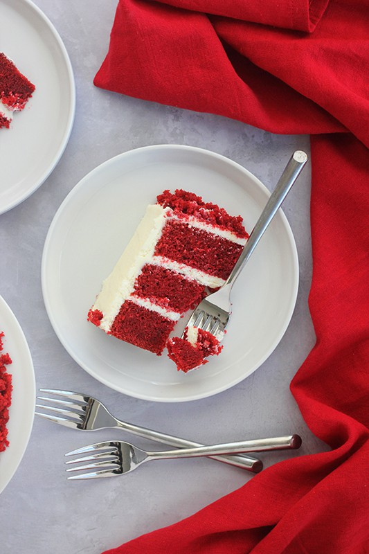 top down photo of red velvet cake slice on white plate with fork