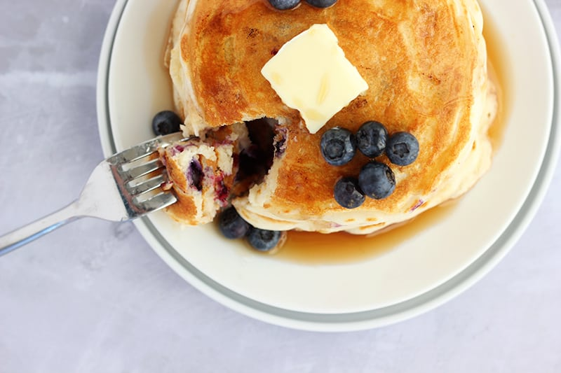 stack of blueberry pancakes on a white plate with a bite cut out