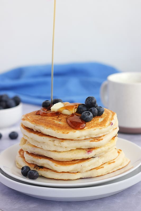 stack of blueberry pancakes with syrup being drizzled on top