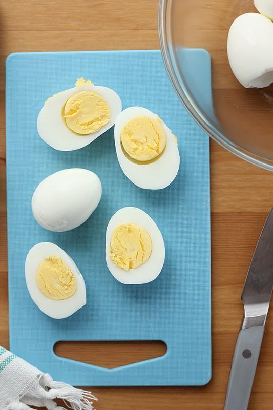 hard boiled eggs on a blue cutting board sliced in h alf
