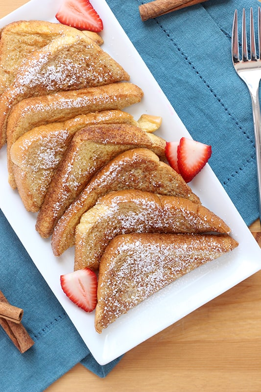 Layers of cooked french toast on a white plate with strawberries
