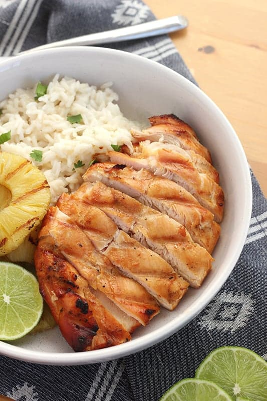 Easy Hawaiian Grilled Chicken sliced and served in a bowl with rice, pineapple, and lime