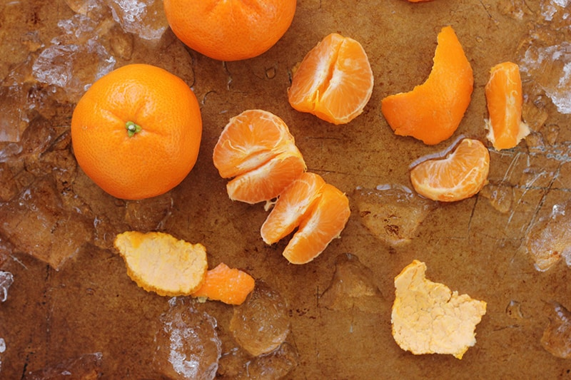 peeled oranges on a baking tray with ice