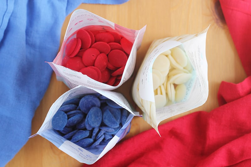 red, white, and blue candy melts in bags on a table