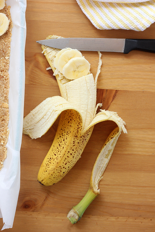 banana with it's peel pulled back and top in slices