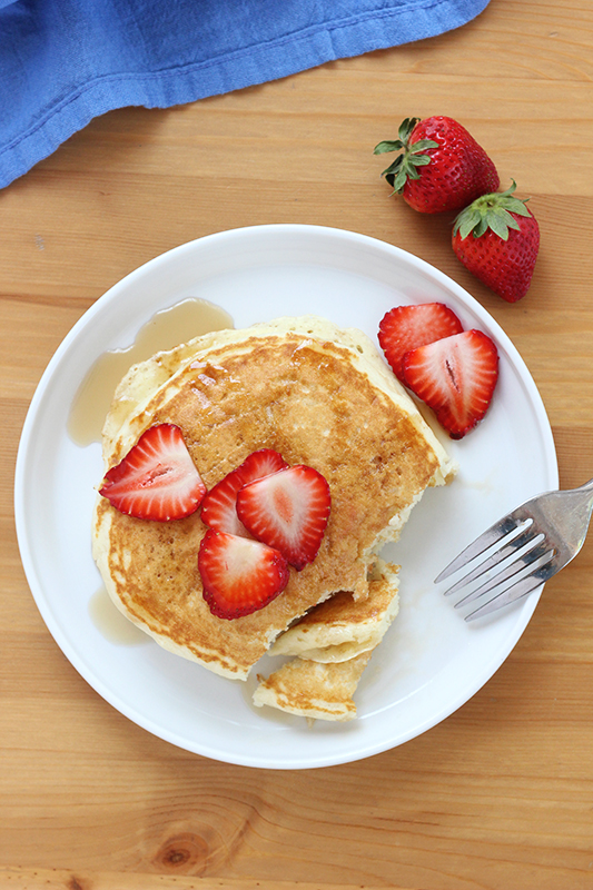 buttermilk pancakes on a white plate with strawberries and syrup