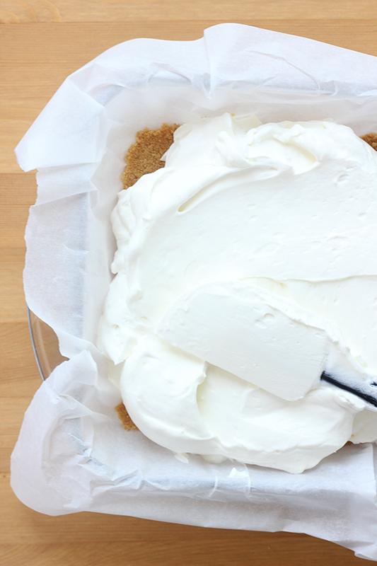 Cheesecake batter spreading over top of graham cracker crust