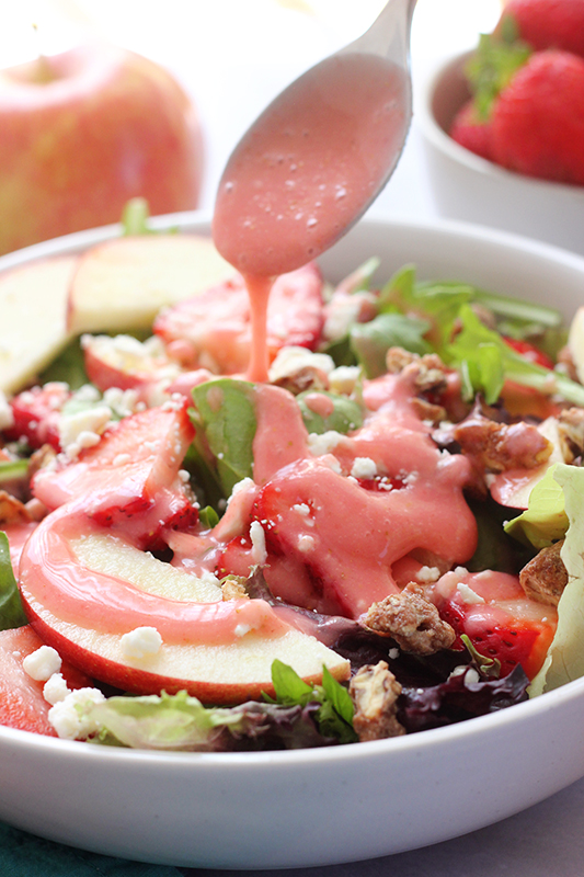Salad dressing being drizzled over strawberry harvest salad