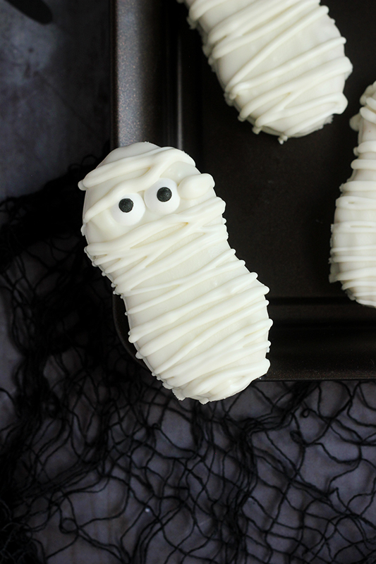 single cookie decorated to look like a mummy balancing on the edge of a black tray