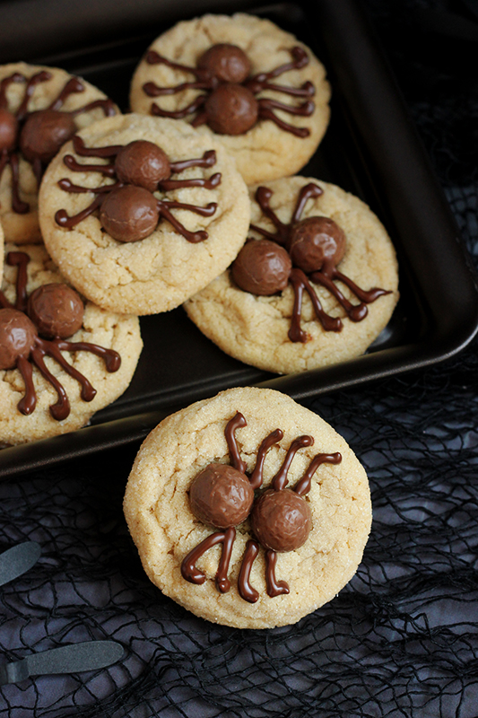 One spider cookie laying sideways on a plate of more cookies