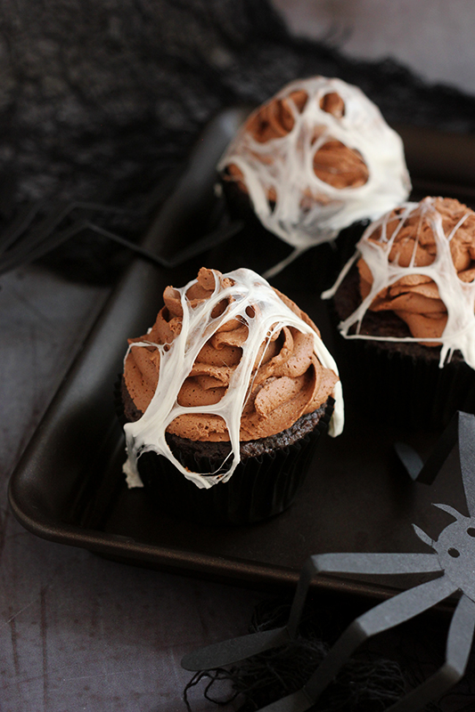 chocolate cupcakes with chocolate frosting and spider web marshmallows on a black tray