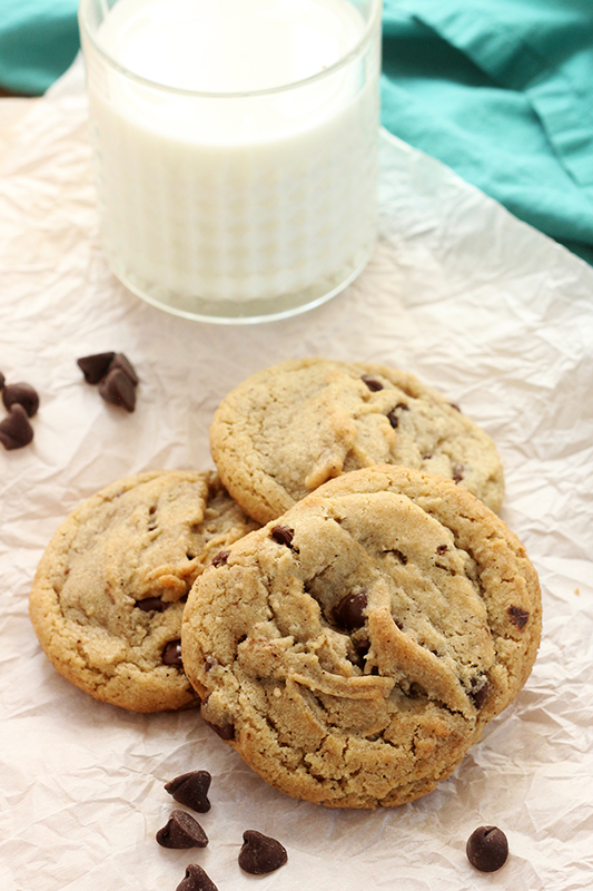 stack of browned butter cookies on parchment paper with extra chocolate chips