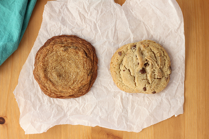 one chilled and baked cookie on parchment next to a flatter darker unchilled baked cookie