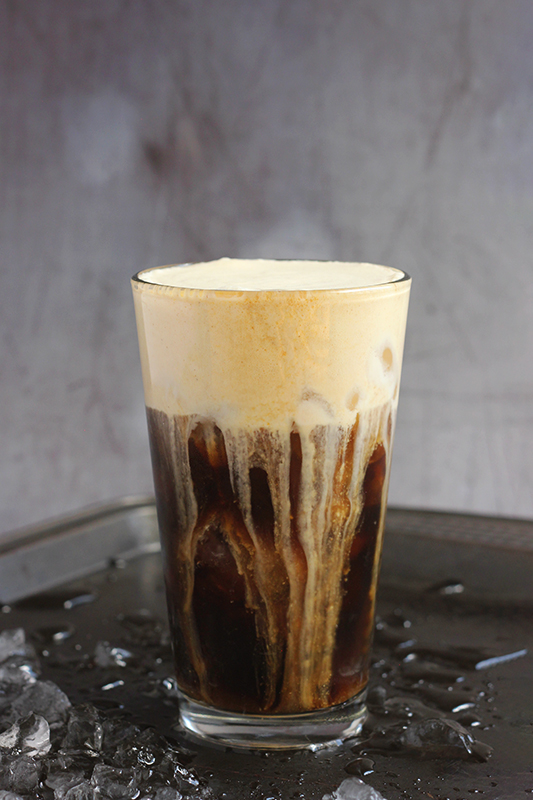 pumpkin sweet cream cold brew in a tall glass on a black baking tray