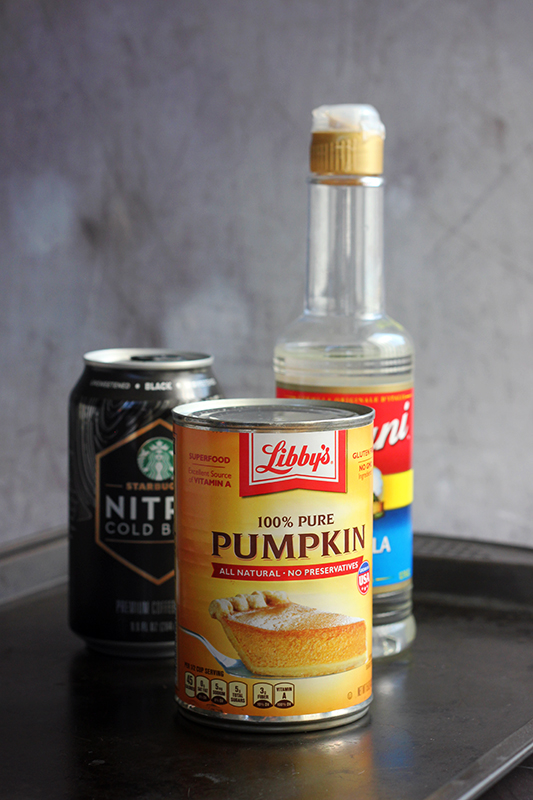 pumpkin puree in a can, canned coffee, and vanilla syrup on a black baking tray