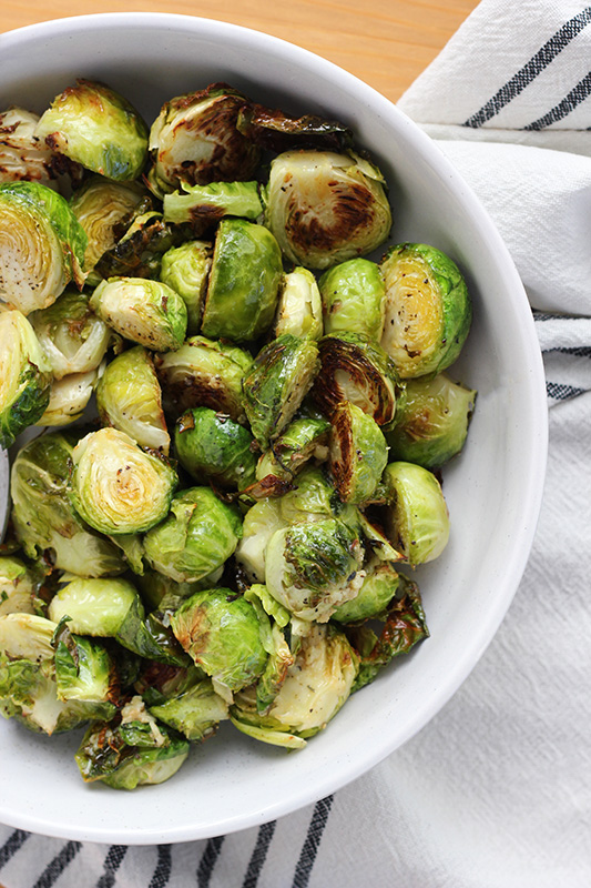 cooked brussels sprout halves in a white bowl with a white napkin under